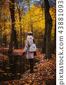 Woman enjoying the silence on the shore of autumn lake. Woman and autumn composition 43881093
