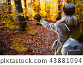 Woman throwing autumn leaves into the air. Carefree, happiness concept. Scenic fall park 43881094