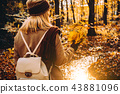 Women holding bouquet of autumn leaves in front of beautiful colorful landscape with a stream and 43881096
