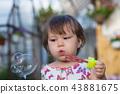 Cute little girl is blowing a soap bubbles 43881675