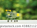 Little shopping cart on forest background 43882112