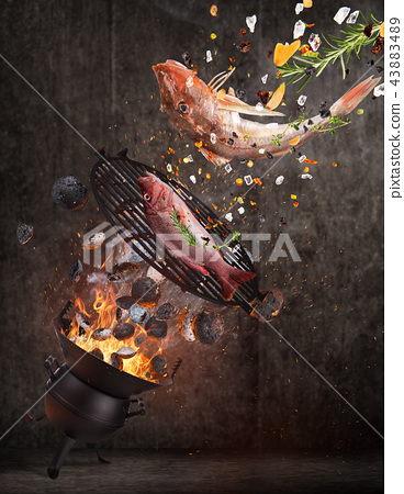 Kettle grill with hot briquettes, cast iron grate and tasty sea fishes flying in the air. 43883489
