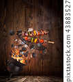 Kettle grill with hot briquettes, cast iron grate and tasty skewers flying in the air. 43883527