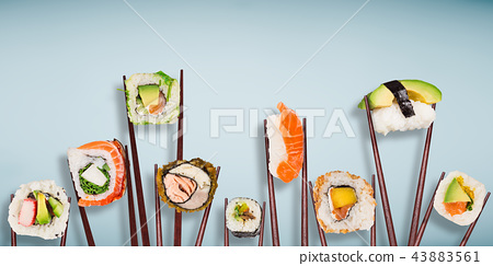 Traditional japanese sushi pieces placed between chopsticks, separated on light blue pastel background. 43883561