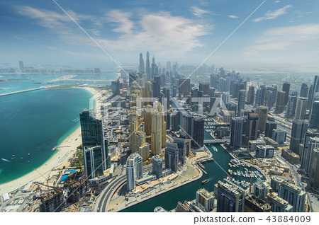 Aerial view of modern skyscrapers and sea in the background in Dubai, UAE. 43884009