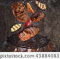 Kettle grill with hot briquettes, cast iron grate and tasty meats flying in the air. 43884083