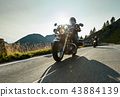 Motorcycle driver riding japanese high power cruiser in Alpine highway on famous Hochalpenstrasse, Austria. 43884139
