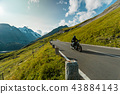 Motorcycle driver riding in Alpine highway on famous Hochalpenstrasse, Austria, Europe. 43884143