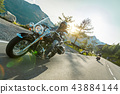 Motorcycle driver riding japanese high power cruiser in Alpine highway on famous Hochalpenstrasse, Austria. 43884144