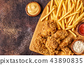 Fried chicken wings with french fries. 43890835
