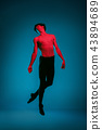 The male athletic ballet dancer performing dance on blue background. Studio shot. Ballet concept 43894689