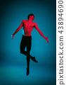 The male athletic ballet dancer performing dance on blue background. Studio shot. Ballet concept 43894690