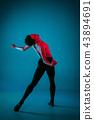 The male athletic ballet dancer performing dance on blue background. Studio shot. Ballet concept 43894691