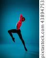 The male athletic ballet dancer performing dance on blue background. Studio shot. Ballet concept 43894753