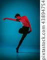 The male athletic ballet dancer performing dance on blue background. Studio shot. Ballet concept 43894754