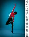 The male athletic ballet dancer performing dance on blue background. Studio shot. Ballet concept 43894755