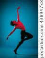 The male athletic ballet dancer performing dance on blue background. Studio shot. Ballet concept 43894758
