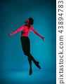 The male athletic ballet dancer performing dance on blue background. Studio shot. Ballet concept 43894783