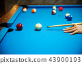 Pool balls on the blue felt pool table with player 43900193