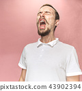 Young handsome man with beard sneezing, studio portrait 43902394
