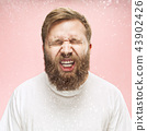 Young handsome man with beard sneezing, studio portrait 43902426