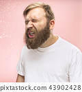 Young handsome man with beard sneezing, studio portrait 43902428