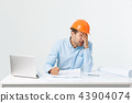 Focused serious hardworking engineer busy working on big architectural project late, sitting at his 43904074
