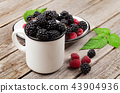 Cup of ripe blackberries and raspberries 43904936