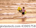 A boy holds a surfboard, he is learning to play it 43905758