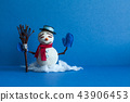 Comical snowman on blue background. Winter holiday traditional snowman character with scarf mittens 43906453
