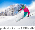 Skier skiing downhill in high mountains 43909582