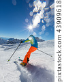 Skier skiing downhill in high mountains 43909618
