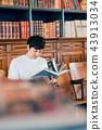 讀一本書的一個人在圖書館裡 43913034