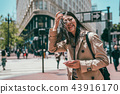 woman standing in street and looking happily 43916170