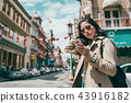 girl standing and using her phone in chinatown 43916182