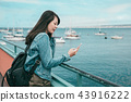 teen girl checking her smartphone at the port 43916222