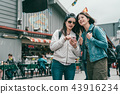 sisters searching shops on smartphone 43916234
