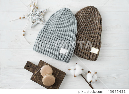Knitted hats, cotton sprigs, macaroons close-up on a white 43925431