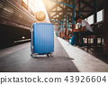 Suitcases with traveller sitting. 43926604