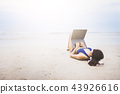 A asia women lying on the beach for working. 43926616