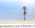 A woman in bikini stand alone on the beach happily 43926617