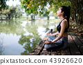 young women meditate while doing yoga. 43926620