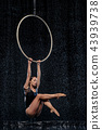 Beautiful female acrobat hanging with graceful pose on aerial hoop under rain on black background 43939738