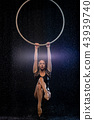 Beautiful female acrobat hanging on aerial hoop under rain on black background 43939740