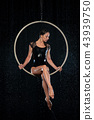 Beautiful female acrobat sitting in aerial hoop under rain on black background 43939750