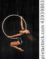A young girl performs the acrobatic elements in the aerial ring. Aqua Studio shooting performances 43939863
