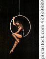 Beautiful female acrobat sitting in aerial hoop under rain on black background 43939889