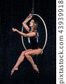 Beautiful female acrobat sitting in aerial hoop under rain on black background 43939918