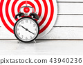 Dartboard with Alarm Clock on white wood. 43940236