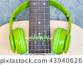 green headphone on acoustic guitar 43940626